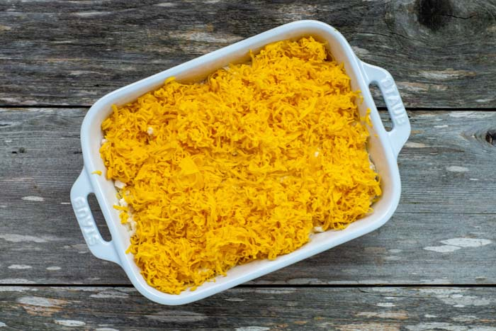 Casserole dish covered with shredded cheddar cheese on a wooden surface