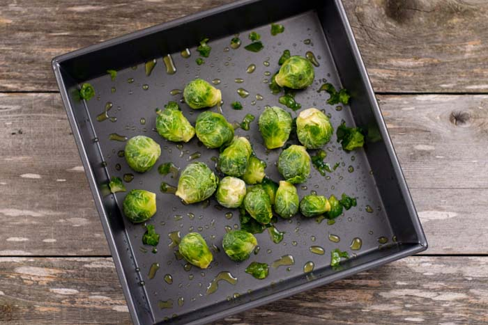 Brussels sprouts covered in oil in a square metal baking dish on a wooden surface