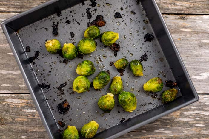 Cooked Brussels sprouts in a square metal baking dish on a wooden surface