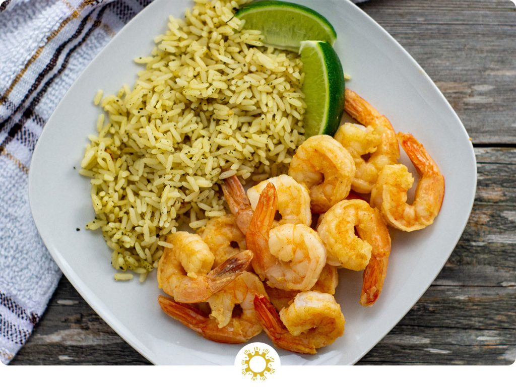 Ginger-lime shrimp next to cilantro and lime shrimp with lime wedges on a square white plate next to a white and brown towel all on a wooden surface (with logo overlay)