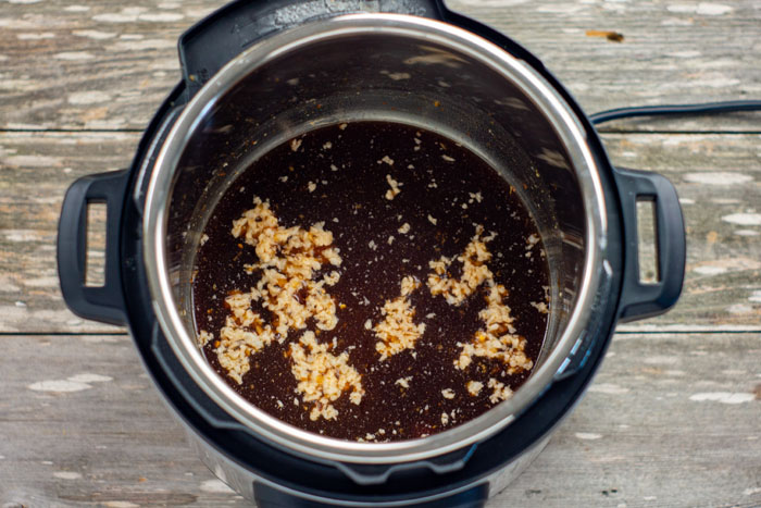 Sauce mixture in an instant pot on a wooden surface