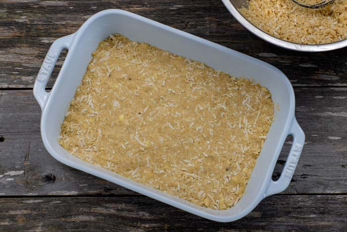 Coconut crust pressed into a white casserole dish next to a stainless steel bowl with more coconut mixture on a wooden surface