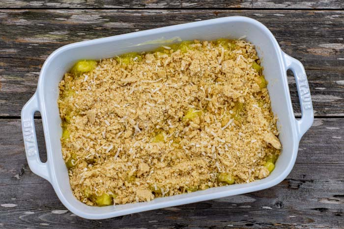 Coconut topping on cooked pineapple in a white casserole dish on a wooden surface