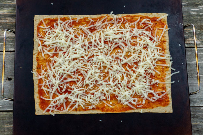 Flatbread covered with pizza sauce and shredded mozzarella cheese on a baking stone on a wooden surface