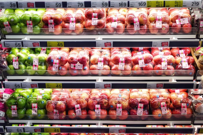 Apples wrapped in plastic in a refrigerated shelf at the grocery store