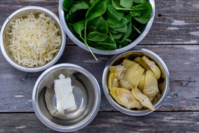 Stainless steel bowls with shredded cheese, spinach leaves, artichoke hearts, and cream cheese all on a wooden surface
