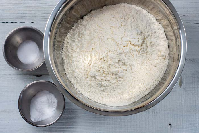 Flour, salt, and baking soda in stainless steel bowls on a white wooden surface