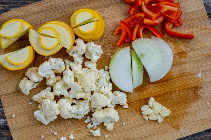 Sliced squash, red bell pepper, onion, garlic, and chopped cauliflower on a bamboo board on a wooden surface