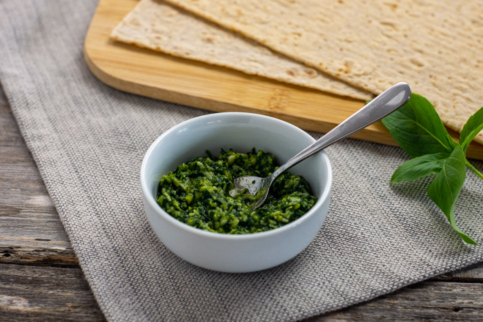 Thai basil pesto in a small round white bowl with a small spoon next to a piece of basil and a bamboo tray with flatbread pieces all on a grey placemat on a wooden surface