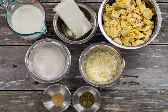 Ingredients for tortellini alfredo in stainless steel bowls on a wooden surface