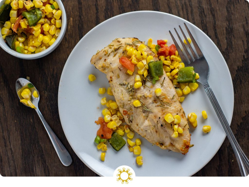 Fresh summer relish on top of a grilled chicken breast with a stainless steel fork on a round white plate with a round white bowl of summer relish behind all on a wooden surface (with logo overlay)