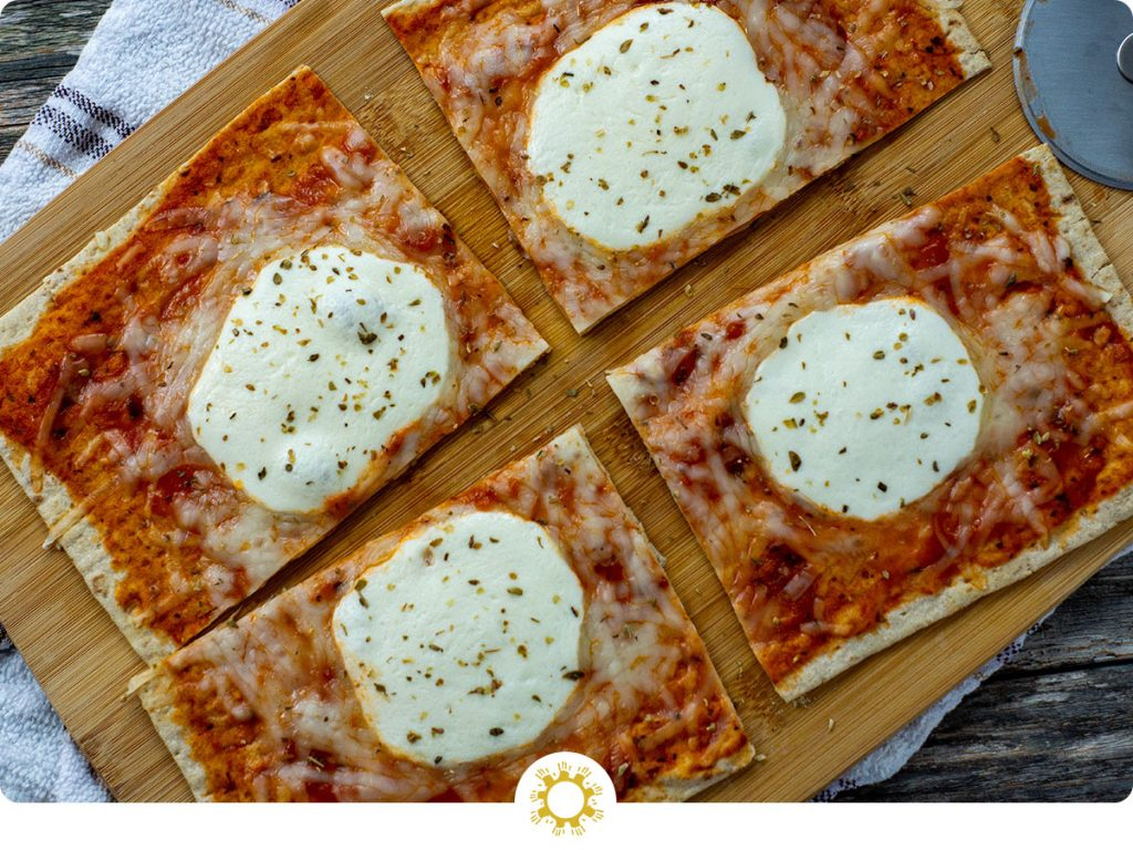 Super Easy Pizza Flatbread on a bamboo tray on top of a white and brown towel on a wooden surface (with logo overlay)