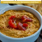 Roasted red pepper hummus topped with oil, paprika, and red peppers in a round white dish with a pita bread behind on a wooden surface (with title overlay)
