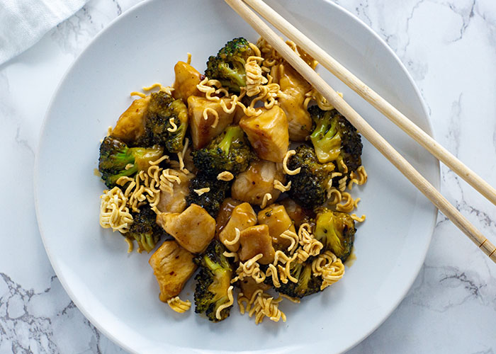 Sweet and Sour Chicken and Broccoli with Ramen Noodles on a round white plate with wooden chopsticks all on a white and grey marble surface