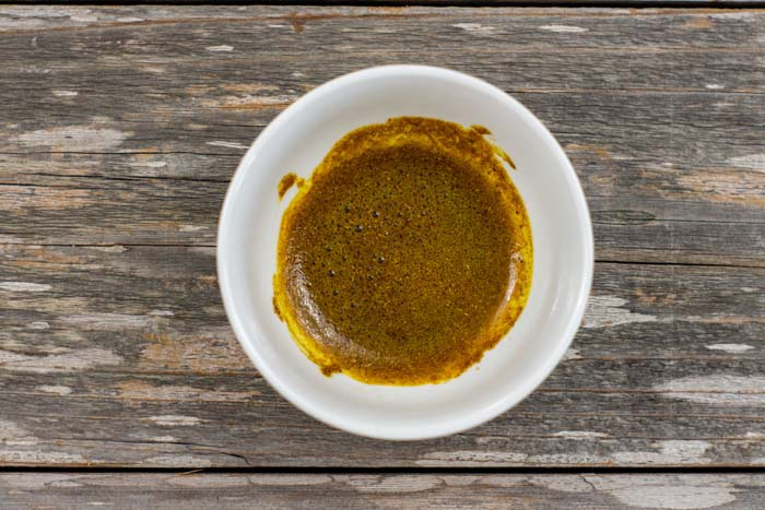 Warmed curry powder in oil in a small round white bowl on a wooden surface