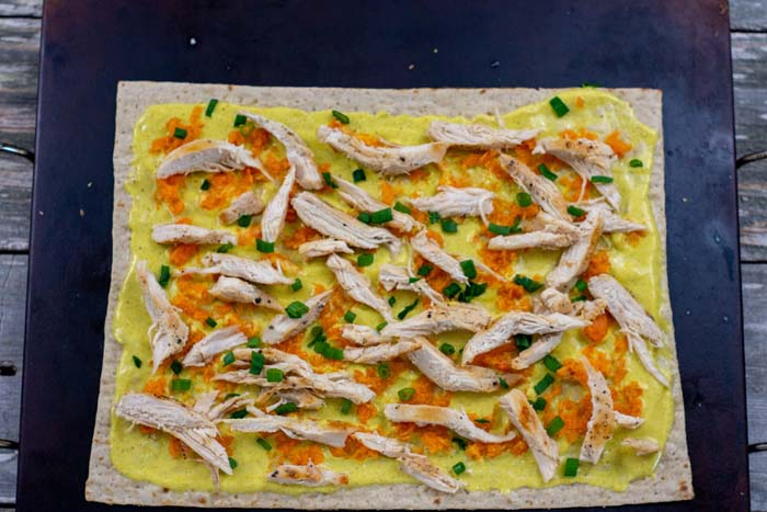 Curry sauce topped with carrots, chicken, and green onions spread on a piece of flatbread on a baking stone on a wooden surface