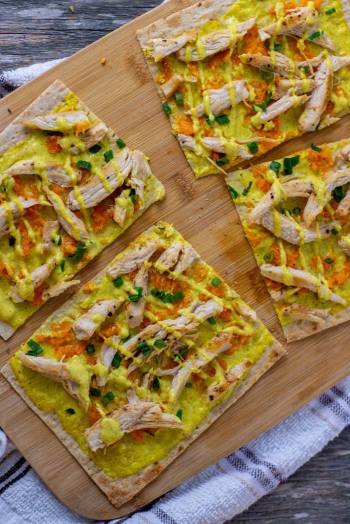 Chicken Curry Flatbread on a bamboo tray on a white and brown towel on a wooden surface (vertical)