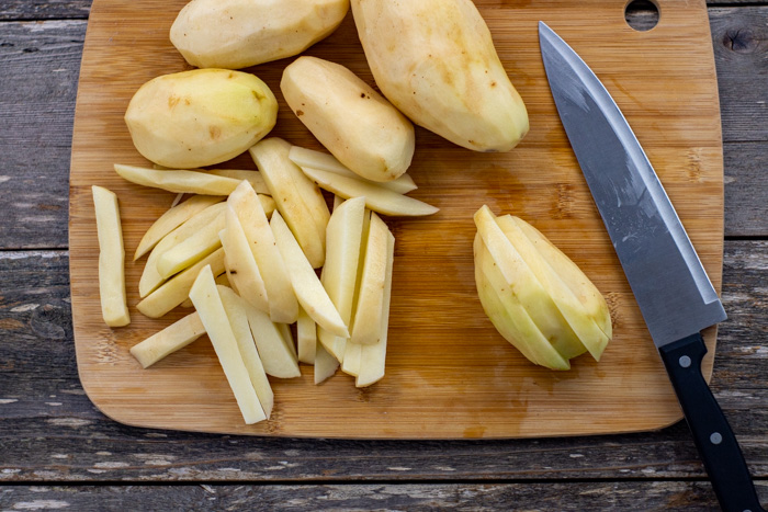 Potatoes on a bamboo board with some cut into strips next to a chef's knife all on a wooden surface