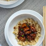 Orange Chicken in the Instant Pot on top of a bed of rice in a round white bowl on a round white plate next to bamboo chopsticks with another serving behind on a grey placemat on a white wooden surface (with title overlay)