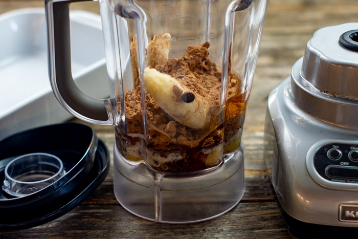 Ingredients for paleo brownies in a blender on a wooden surface