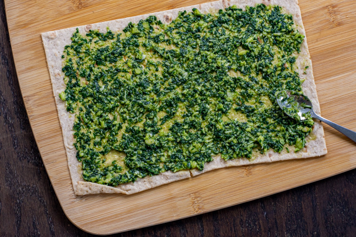 Green pesto spread on a piece of flatbread on a bamboo board on a wooden surface