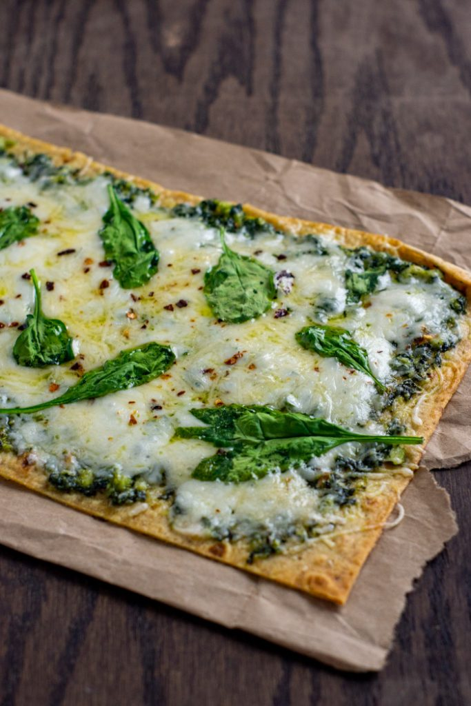 Pesto flatbread topped with shredded cheese and spinach leaves on brown parchment paper on a wooden surface (vertical)