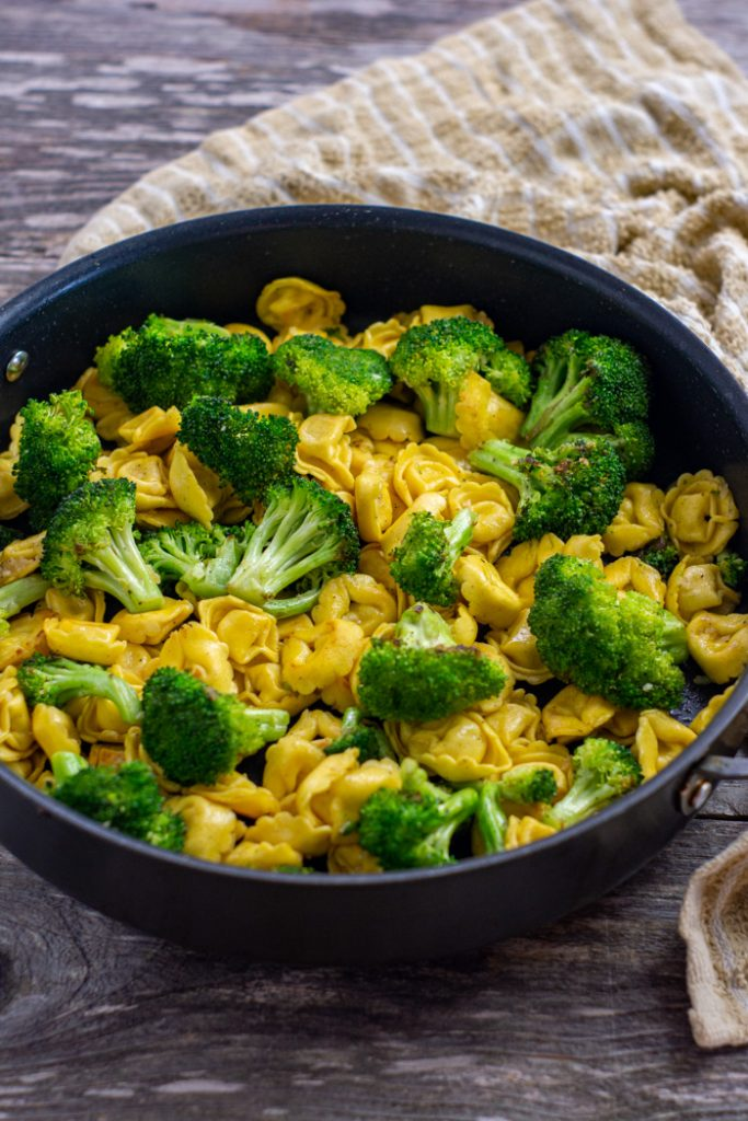 Toasted cheese tortellini and broccoli in a large skillet with a tan and white towel behind all on a wooden surface (vertical)