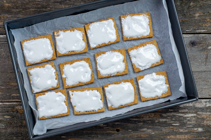 Graham cracker squares topped with marshmallow fluff on a piece of parchment paper on a baking sheet on a wooden surface