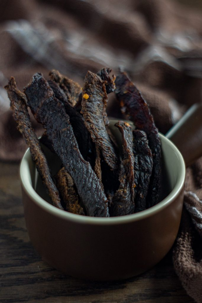 Sticks of beef jerky in a round brown and tan bowl with a brown and white towel behind all on a wooden surface (vertical)