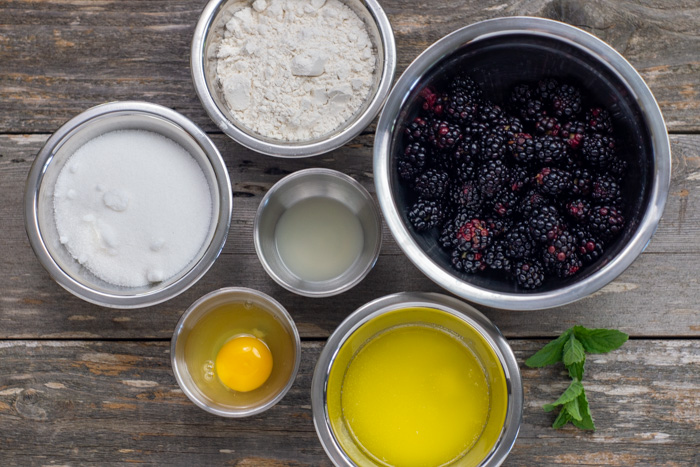 Blackberry cobbler ingredients in stainless steel bowls on a wooden surface: sugar, flour, blackberries, melted butter, egg, and lemon juice