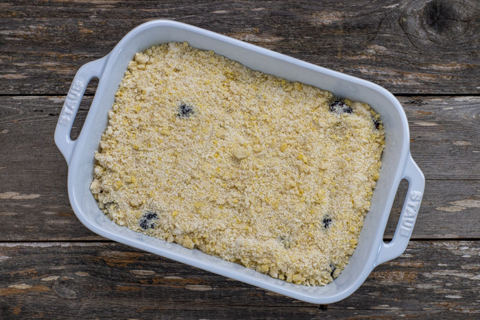 Blackberries covered with cobbler topping in a white casserole dish on a wooden surface
