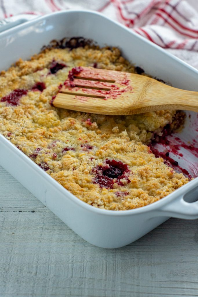 Blackberry cobbler in a white casserole dish with a wooden spoon next to a red and white towel all on a white wooden surface (vertical)