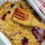 Blackberry cobbler in a white casserole dish with a wooden spoon next to a red and white towel all on a white wooden surface (with title overlay)