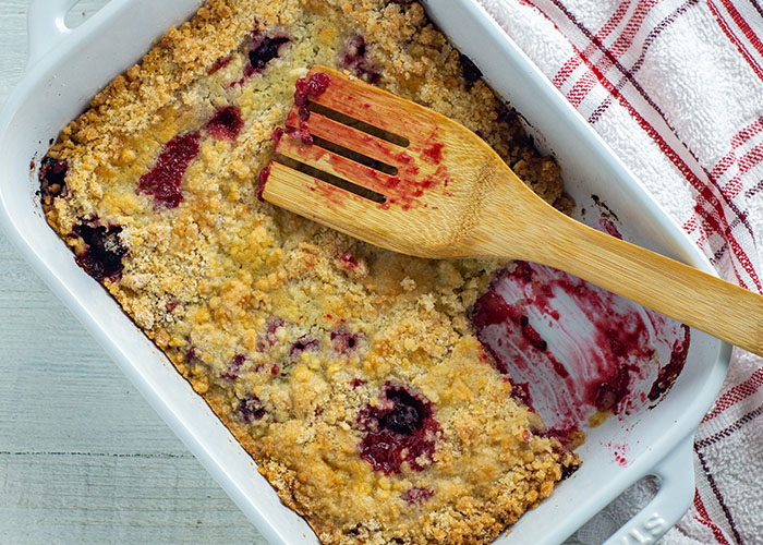 Blackberry cobbler in a white casserole dish with a wooden spoon next to a red and white towel all on a white wooden surface