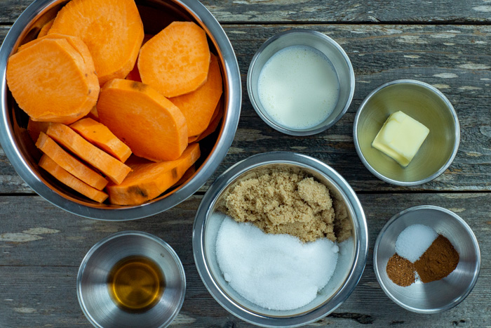 Ingredients for candied yams in stainless steel bowls on a wooden surface: sliced sweet potatoes, cream, butter, spices, sugars, and vanilla extract