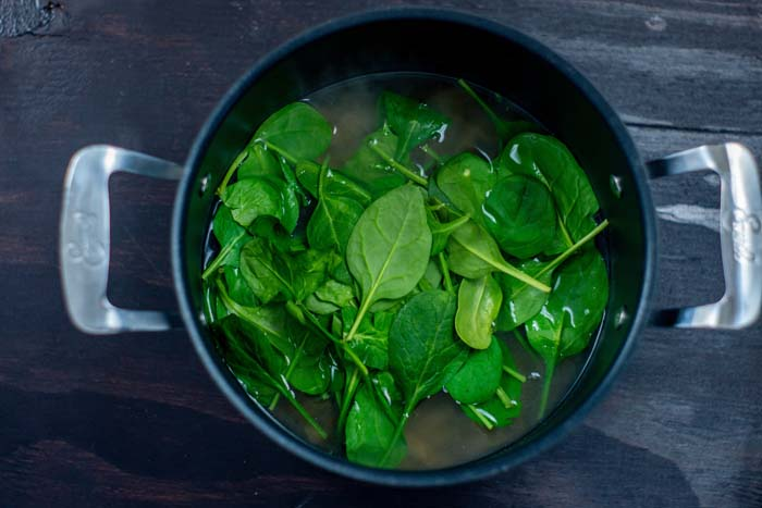 Spinach leaves on top of boiling noodles in a large stockpot on a dark wooden surface