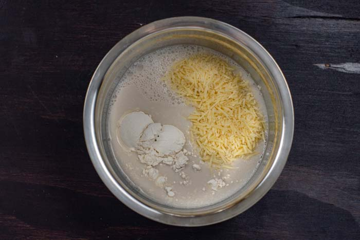 Milk, flour, and shredded cheese in a stainless steel bowl on a dark wooden surface