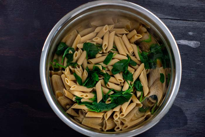 Cooked pasta noodles with wilted spinach in a stainless steel bowl on a dark wooden surface