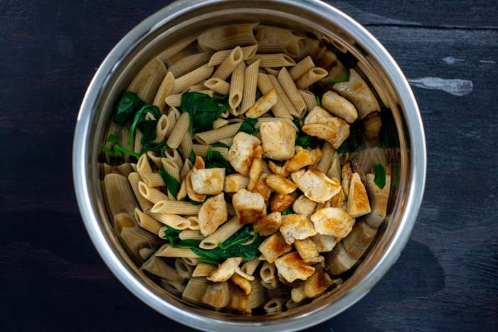 Cooked pasta, wilted spinach, and cooked pieces of chicken in a stainless steel bowl on a dark wooden surface