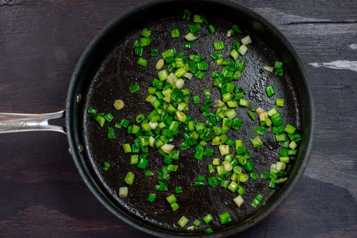 Chopped green onion in a large skillet on a dark wooden surface