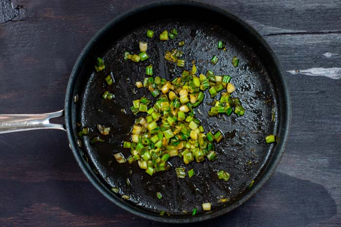 Chopped green onion in lemon juice cooking in a large skillet on a dark wooden surface