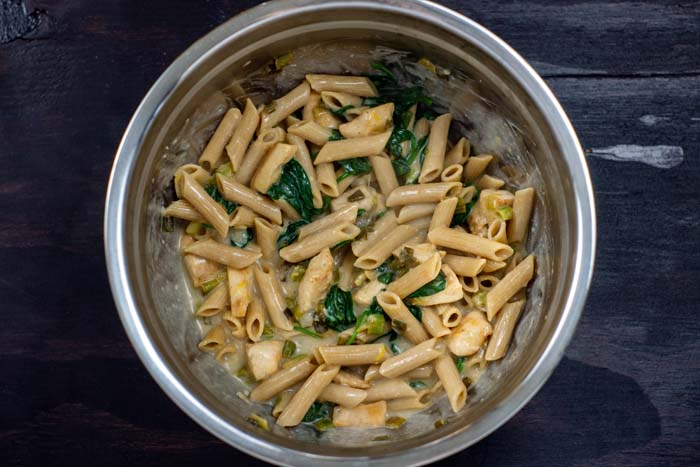 Cooked pasta with wilted spinach and sauce in a stainless steel bowl on a dark wooden surface