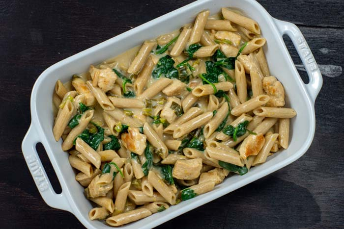 Cooked noodles, wilted spinach, and cooked chicken pieces covered with sauce in a white casserole dish on a dark wooden surface