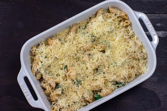 Cooked noodles with spinach and chicken covered with shredded cheese in a white casserole dish on a dark wooden surface