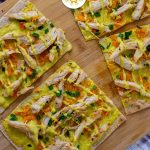 Chicken Curry Flatbread on a bamboo tray on a white and brown towel on a wooden surface (with title overlay)