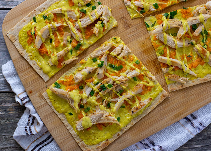 Chicken Curry Flatbread on a bamboo tray on a white and brown towel on a wooden surface