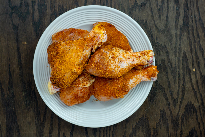 Chicken drumsticks seasoned with bbq seasoning on a round white plate on a wooden surface