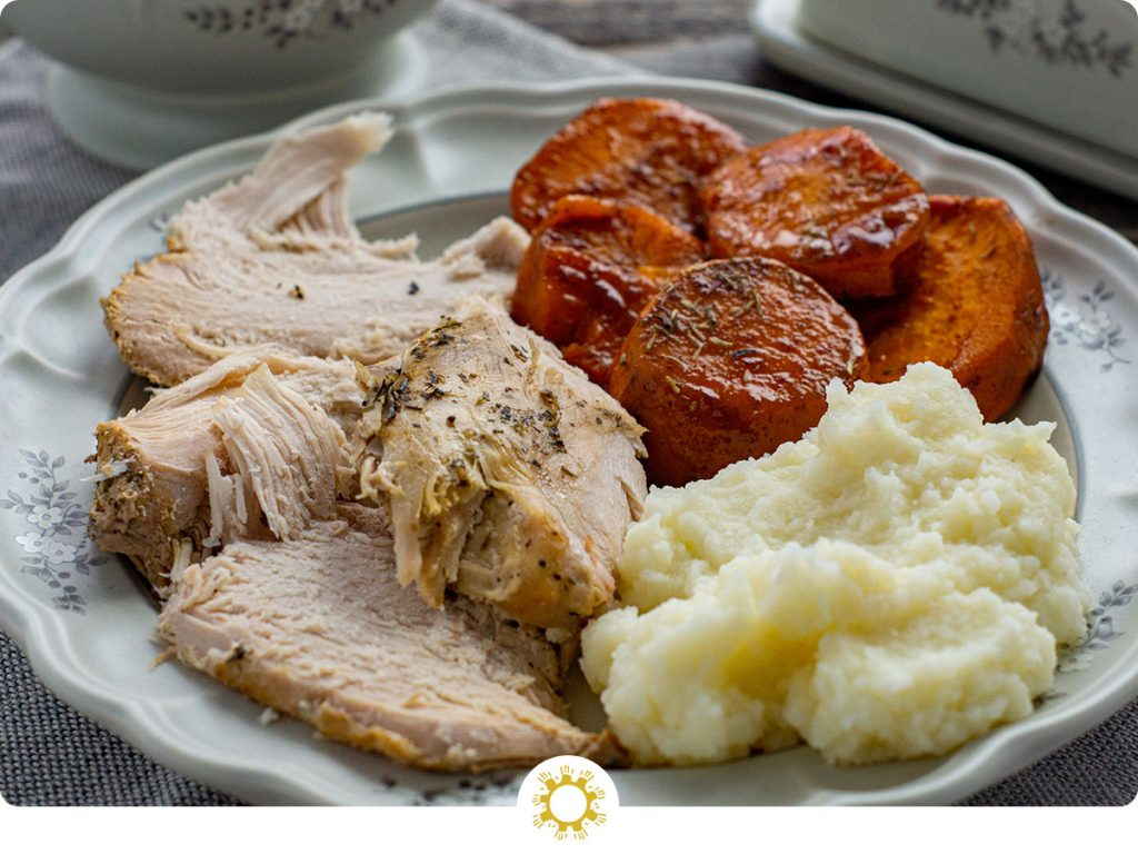 Instant pot turkey with candied yams and mashed potatoes on a grey plate (with logo overlay)