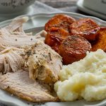 Instant pot turkey with candied yams and mashed potatoes on a grey plate
