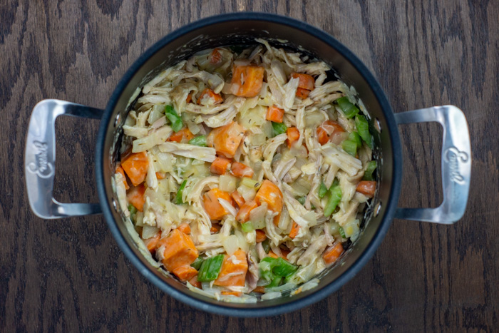 Diced vegetables and shredded chicken in a sauce in a large stockpot on a wooden surface
